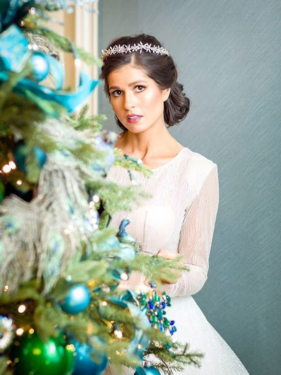 bride to be behind a christmas tree